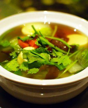 Soupe aux légumes avec champignons, tofu et feuilles de coriandre.
